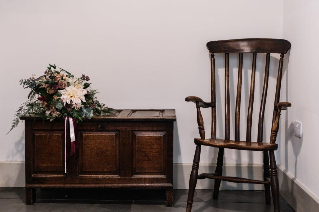 bridal bouquet next to antique chair