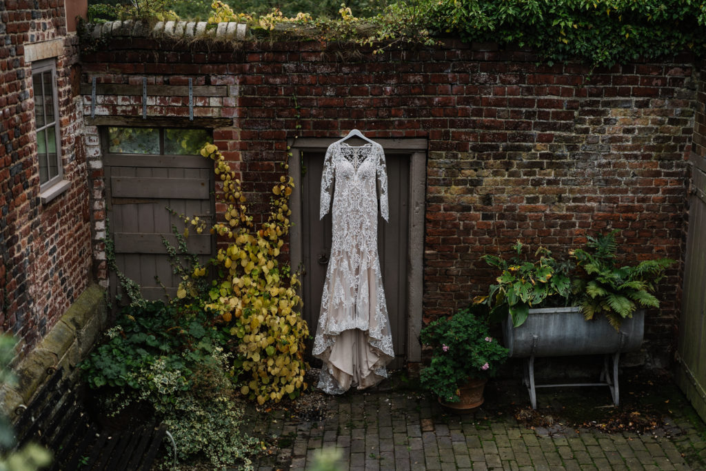 wedding dress hanging on an exterior wall at Pimhill Barn, Shropshire